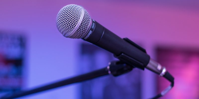 A corded microphone on a stand in a dimly lit room